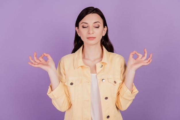 Portret van kalm lief meisje mediteert yoga beoefening sluit ogen op violette achtergrond