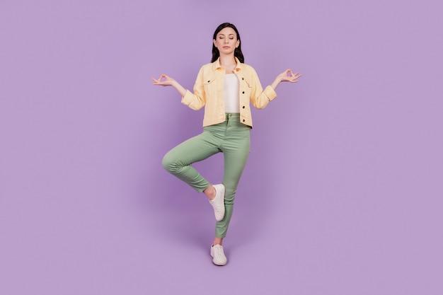 Portret van kalm vreedzaam meisje mediteren dichte ogen harmonie concept op paarse achtergrond