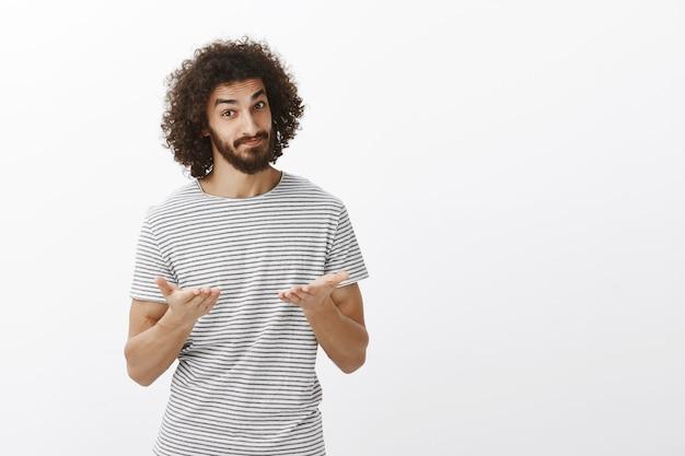 Portret van kalme en zelfverzekerde aantrekkelijke werkgever in gestreept overhemd, gelegenheid geven om mening te uiten, wijzend met handpalmen