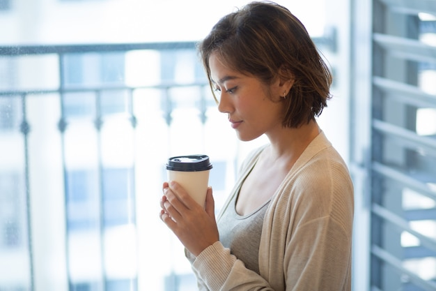 Portret van kalme jonge vrouw die zich met koffiekop bevindt