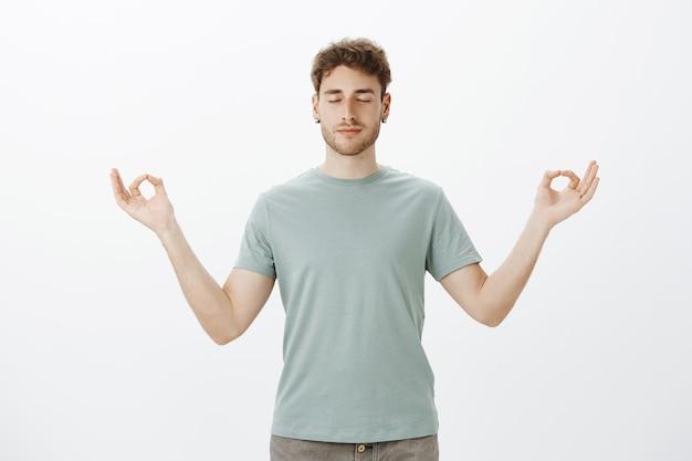 Portret van kalme knappe blanke man in t-shirt, glimlachend en ontspannen gevoel, staande met gespreide handen in zen gebaar en gesloten ogen