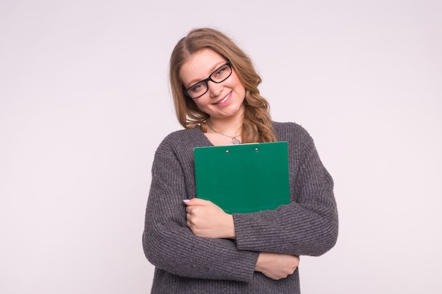 Portret van kalme slimme jonge vrouw met groenboekmap op witte muur
