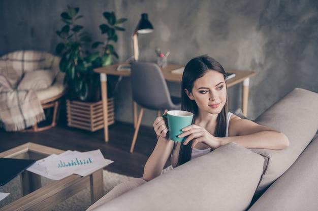 Portret van kalme tevreden meisjesmanager drinkt hete koffierest