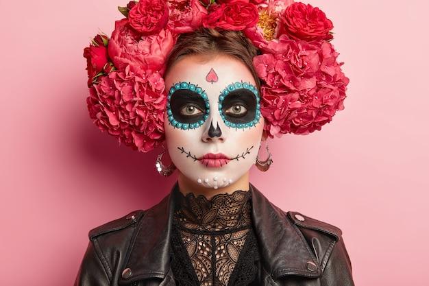 Portret van kalme vrouw viert de dag van de dood, heeft make-up van suikerschedels, donkere kringen bij de ogen, een geschilderde glimlach, denkt dat de dood een natuurlijk onderdeel is van de menselijke cyclus, draagt traditionele mexicaanse kledij.