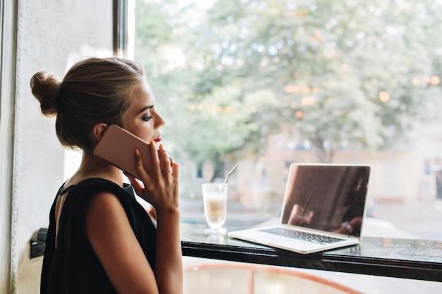 Portret van kant mooie vrouw in zwarte jurk in cafetaria. ze praat aan de telefoon, kijkt op laptop.