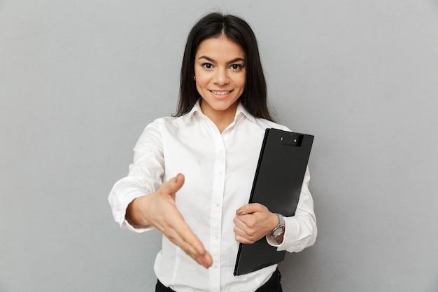 Portret van kantoor vrouw met lang donker haar dragen witte overhemd glimlachend en hand geven om te schudden terwijl map met documenten, geïsoleerd over grijze achtergrond