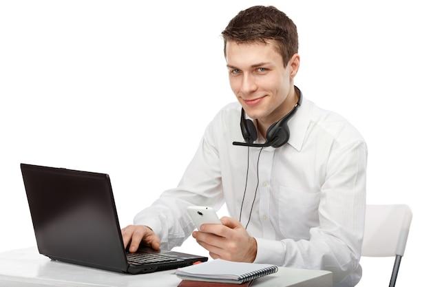 Portret van kantoormedewerker aan een bureau met een computer en een telefoon