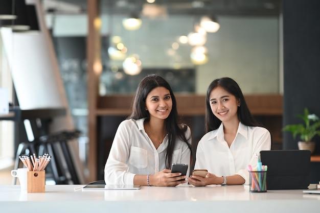 Portret van kantoorvrouwen houden smartphone in de hand terwijl ze aan het bureau zitten