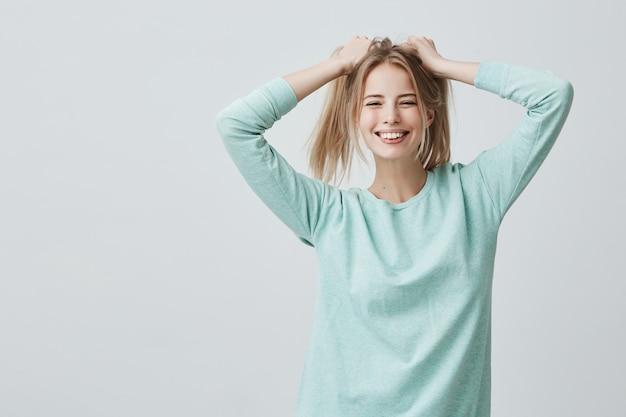 Portret van kaukasisch mannelijk model vrolijk lachend met witte tanden, spelend met haar lang geverfde blonde haar, verheugend gelukkige momenten van haar leven. positieve emoties en gevoelens concept.