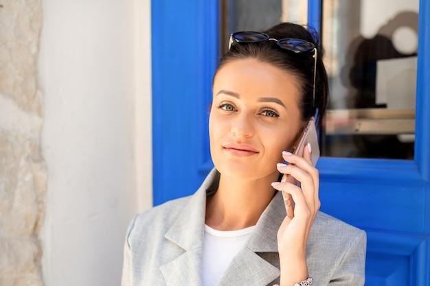 Portret van kaukasische bedrijfsvrouwengesprekken op celtelefoon die grijs kostuum dragen bij de deur
