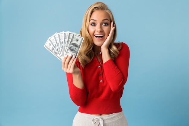 Portret van kaukasische blonde vrouwen20s die de rode ventilator van de overhemdsholding van dollargeld dragen, dat over blauwe muur wordt geïsoleerd
