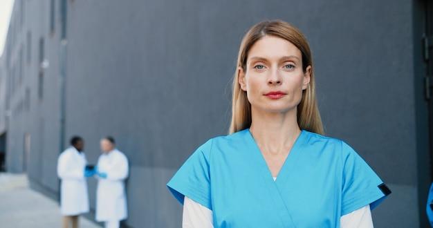 Portret van kaukasische jonge mooie vrouw arts camera kijken en vrolijk glimlachen. vrij vrouwelijke arts glimlach. multi-etnische artsen op achtergrond. medic in witte jurk. detailopname. zoomen.