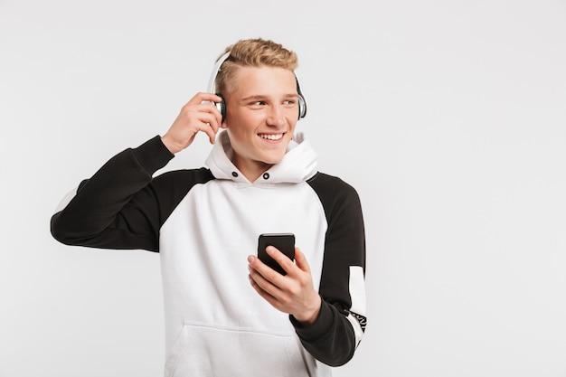 Portret van kaukasische jongere 16-18 jaar oud dragen hoodie glimlachend en luisteren naar muziek op mobiele telefoon via draadloze koptelefoon op wit wordt geïsoleerd