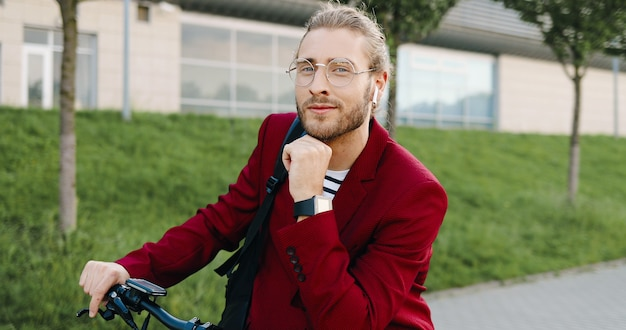 Portret van kaukasische knappe jonge man in rode jas en glazen die openlucht met elektrische autoped staan en naar camera kijken. stijlvolle man bij voertuig op straat in de stad. dolly neergeschoten. inzoomen.
