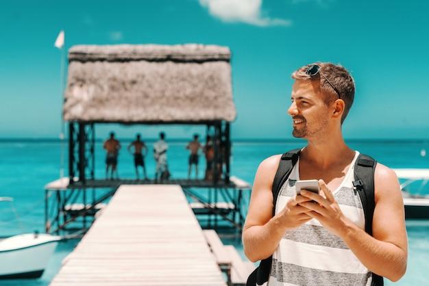 Portret van kaukasische knappe man die slimme telefoon met behulp van terwijl hij op het dok staat en wegkijkt. in achtergrondoceaan. zomervakantie concept.