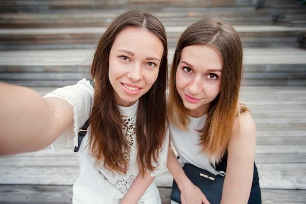 Portret van kaukasische mooie meisjes die selfie buitenshuis maken. jonge toeristenvrienden die bij vakantie gelukkig glimlachen reizen.