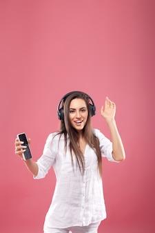 Portret van kaukasische mooie vrouw die aan muziek luistert die draadloze hoofdtelefoons gebruikt