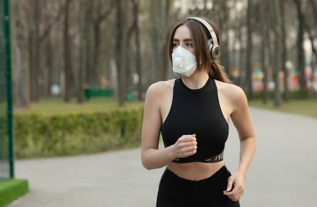 Portret van kaukasische sportieve vrouw die een masker van het medische beschermingsgezicht draagt terwijl het lopen in park. het coronavirus of covid-19 verspreidt zich over de hele wereld.