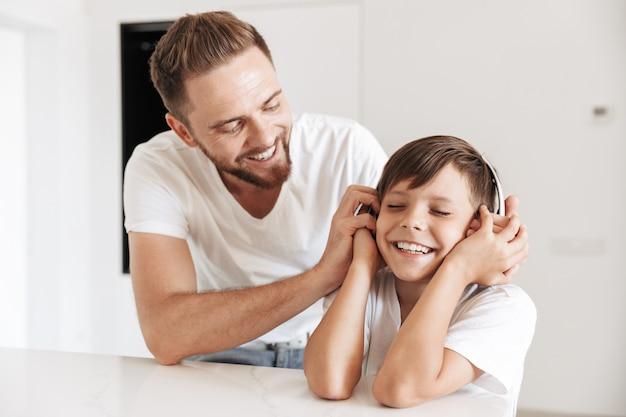 Portret van kaukasische vader en zoon die samen glimlachen, terwijl thuis rusten en naar muziek luisteren via draadloze hoofdtelefoons