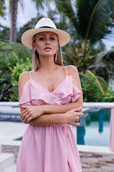Portret van kaukasische vrouw in romantische elegante roze lange jurk op vakantie in luxe rijke villahotel met prachtig uitzicht op tropische palmbomen vrouw in klassieke witte hoed