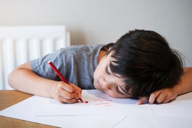 Portret van kind dat een brief schrijft, weinig jongen die rood hart op witboek trekt voor zijn mamma.
