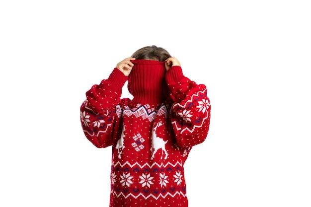 Portret van kind in oversized rode gebreide kersttrui met rendier verbergend gezicht in kraag isol...
