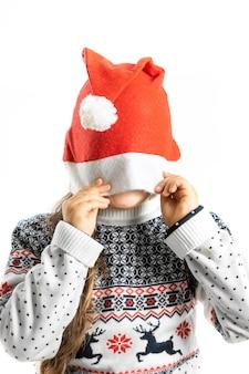 Portret van kind in witte kersttrui met rendieren verbergend gezicht in kerstman hoed geïsoleerd op...