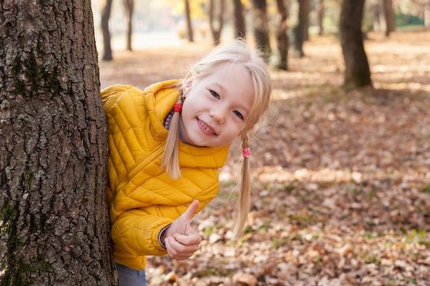 Portret van kind meisje kijkt uit achter boom en duimen opdagen