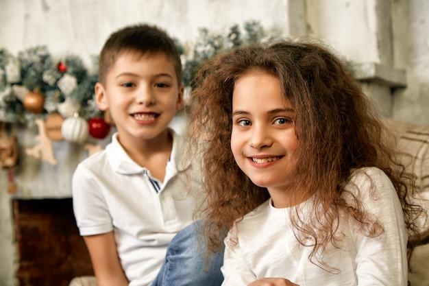 Portret van kinderen die bij kerstmis op giften wachten dichtbij een open haard die met nieuwjaardecor wordt verfraaid. concept kerstmis en kinderen die op een wonder wachten.