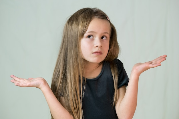 Portret van kindmeisje dat haar schouders ophaalt onschuldig maken ik ken geen uitdrukking.