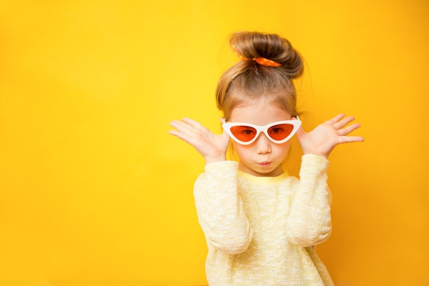 Portret van kindmeisje in glazen op een gele achtergrond. kopieer ruimte