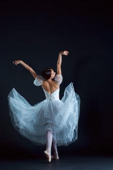 Portret van klassieke ballerina in witte jurk op zwart