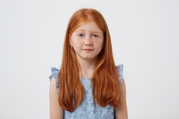 Portret van klein beledigd sproeten roodharig meisje met twee staarten, ontevreden kijkt awey, draagt in blauwe jurk, staat op witte achtergrond.
