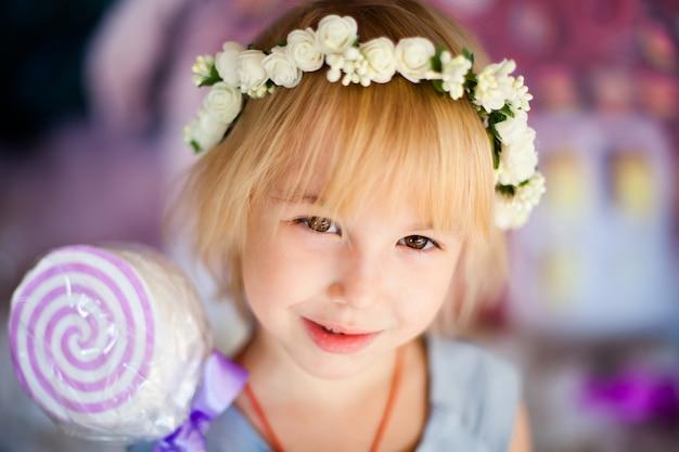 Portret van klein blonde glimlachend meisje met stuk speelgoed suikergoed en witte bloemdiadeem.