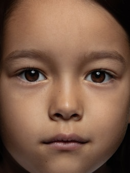 Portret van klein en emotioneel aziatisch meisje close-up. zeer gedetailleerde fotoshoot van een vrouwelijk model met een goed onderhouden huid en een heldere gezichtsuitdrukking. concept van menselijke emoties. kijkend naar de camera.
