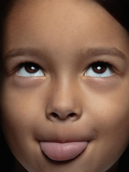 Portret van klein en emotioneel aziatisch meisje close-up. zeer gedetailleerde fotoshoot van een vrouwelijk model met een verzorgde huid en een heldere gezichtsuitdrukking. concept van menselijke emoties. tong hangt uit.