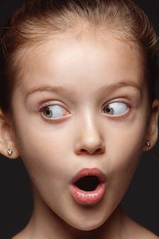Portret van klein en emotioneel kaukasisch meisje close-up. zeer gedetailleerde fotoshoot van een model met een goed onderhouden huid en een heldere gezichtsuitdrukking. concept van menselijke emoties. verbaasd, van opzij kijkend.