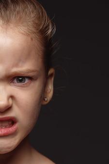 Portret van klein en emotioneel kaukasisch meisje close-up. zeer gedetailleerde fotoshoot van een vrouwelijk model met een goed onderhouden huid en een heldere gezichtsuitdrukking. concept van menselijke emoties. boos, kijkend naar de camera.