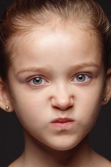 Portret van klein en emotioneel kaukasisch meisje close-up. zeer gedetailleerde fotoshoot van een vrouwelijk model met een goed onderhouden huid en een heldere gezichtsuitdrukking. concept van menselijke emoties. boos, somber.