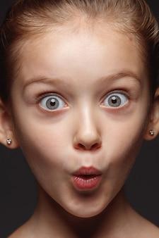 Portret van klein en emotioneel kaukasisch meisje close-up. zeer gedetailleerde fotoshoot van een vrouwelijk model met een goed onderhouden huid en een heldere gezichtsuitdrukking. concept van menselijke emoties. geschokt, vroeg zich af.