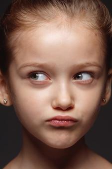 Portret van klein en emotioneel kaukasisch meisje close-up. zeer gedetailleerde fotoshoot van een vrouwelijk model met een goed onderhouden huid en een heldere gezichtsuitdrukking. concept van menselijke emoties. nadenkend, denkend.