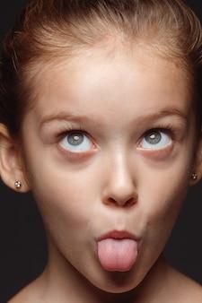 Portret van klein en emotioneel kaukasisch meisje close-up. zeer gedetailleerde fotoshoot van een vrouwelijk model met een goed onderhouden huid en een heldere gezichtsuitdrukking. concept van menselijke emoties. speelse gremaces.
