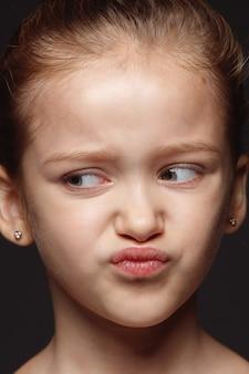 Portret van klein en emotioneel kaukasisch meisje close-up. zeer gedetailleerde fotoshoot van een vrouwelijk model met een goed onderhouden huid en een heldere gezichtsuitdrukking. concept van menselijke emoties. walgelijk.