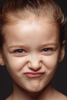 Portret van klein en emotioneel kaukasisch meisje close-up. zeer gedetailleerde fotoshoot van een vrouwelijk model met een verzorgde huid en een heldere gezichtsuitdrukking. concept van menselijke emoties. speelse gremaces.