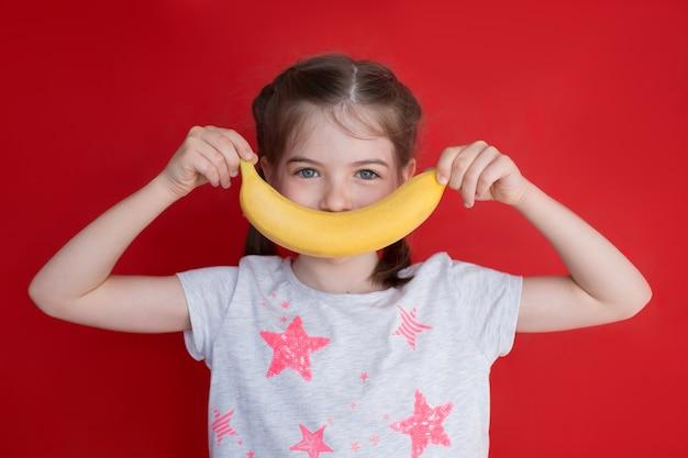 Portret van klein mooi meisje met banaanglimlach op rood