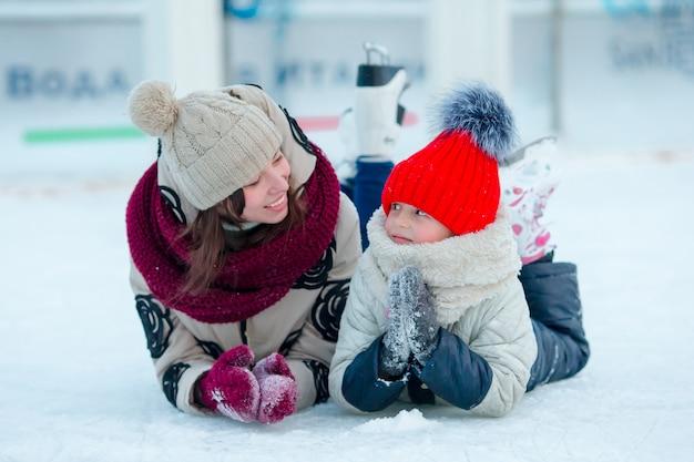 Portret van klein schattig meisje en jonge vrouw schaatsen