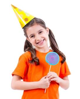Portret van klein schattig meisje in oranje t-shirt en feestmuts met gekleurd snoep - geïsoleerd op wit