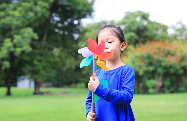 Portret van kleine aziatische blazende de windturbine van het jong geitjemeisje in de de zomertuin.