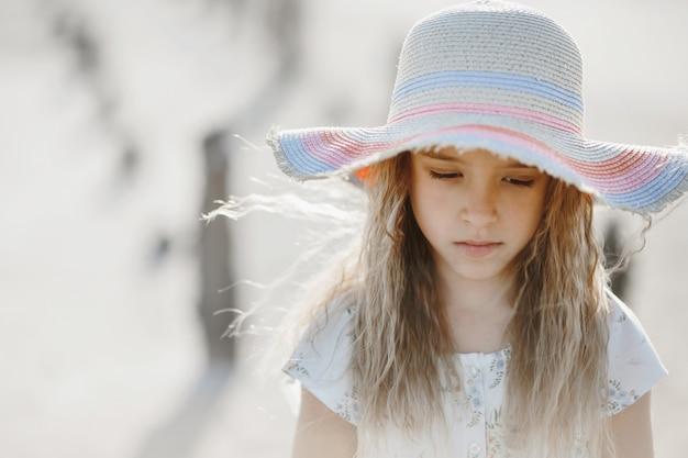 Portret van kleine blonde blanke meisje in de hoed met droevig gezicht