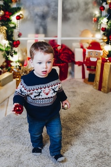 Portret van kleine blonde jongen in ingerichte studio en spelen met kerstballen